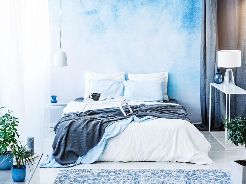Grey blanket on bed in blue bedroom interior with plants and white lamp on table