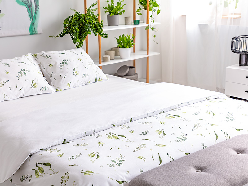 Close-up of a bed dressed in organic cotton green plants pattern white linen in a sunny bedroom interior.