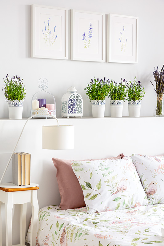 Lamp on table next to bed with patterned sheets in bedroom interior with flowers and posters.