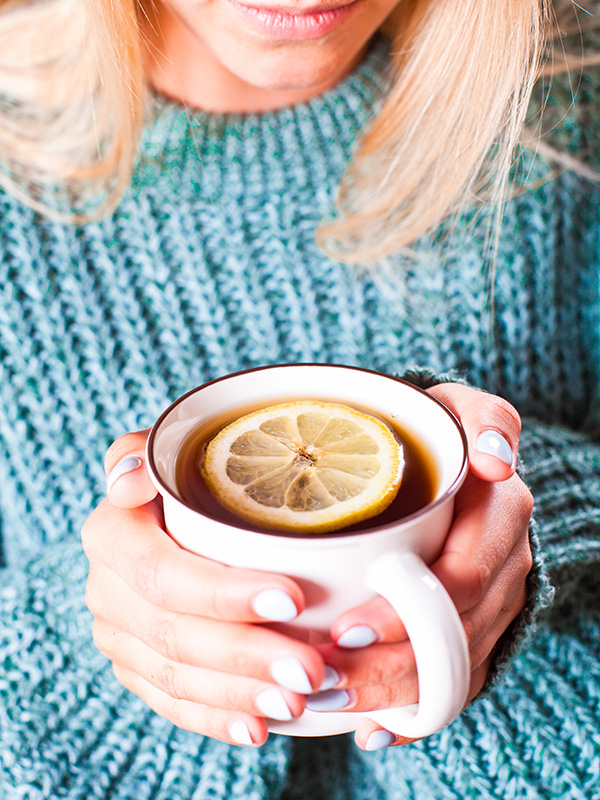 Female hands holding mug of hot tea with lemon