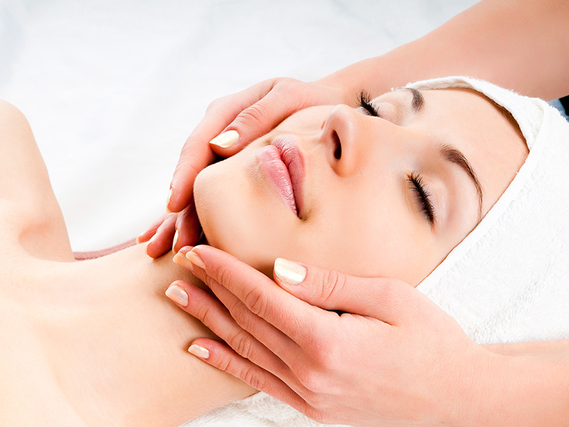 Beautiful young woman receiving facial massage with closed eyes in a spa centre