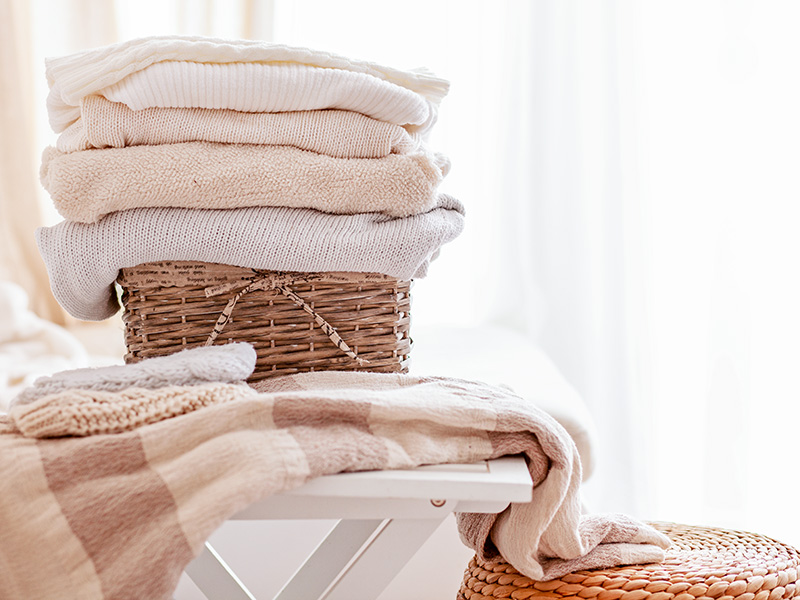 Stack of cosy knitted sweaters in wicker basket