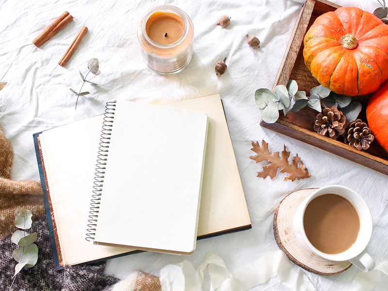 Autumn breakfast in bed with a notepad, book, coffee, candle, eucalyptus leaves and pumpkins on wooden tray.