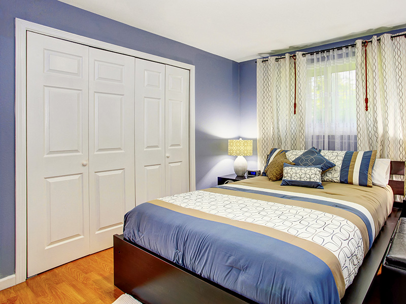 Black and blue bedroom interior with built-in wardrobe and hardwood floor