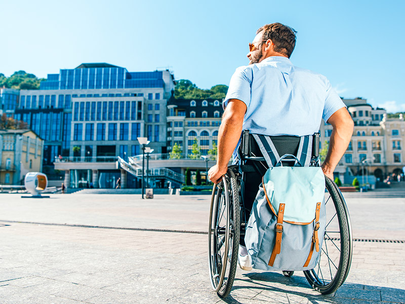 Man in wheelchair wearing a blue shirt and with a blue rucksack, seen from behind looking out at a city street