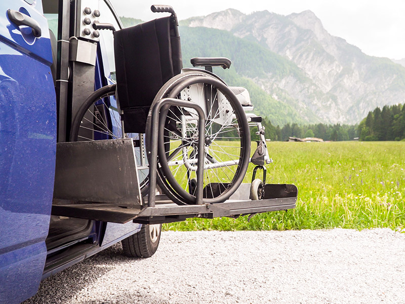 Photo of black electric lift on wheelchair accessible vehicle, with mountains in the back