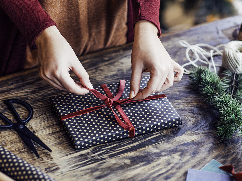 Woman tying a red ribbon on a Christmas present wrapped in spotted paper.