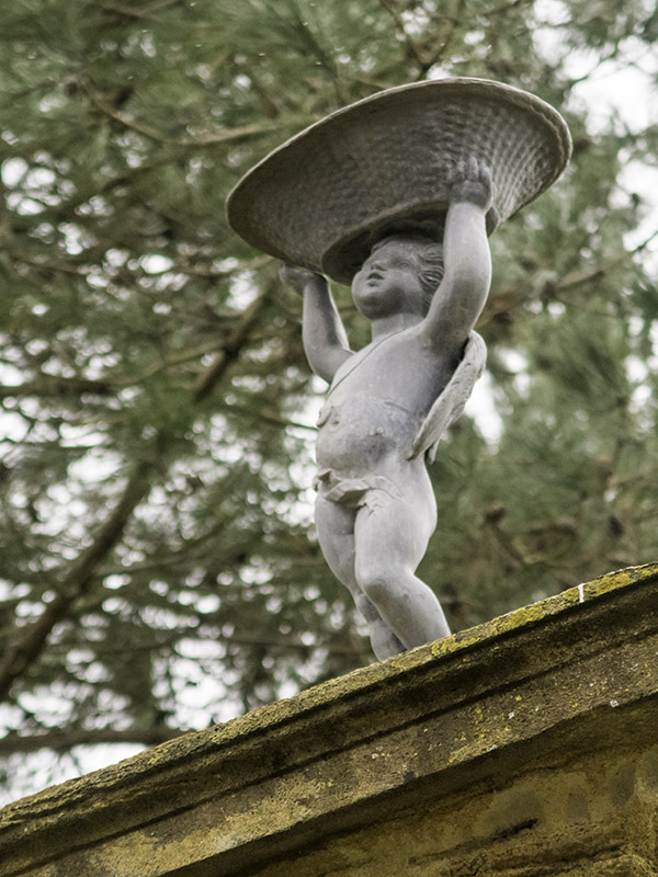 A small statue of a cherub in the gardens at Hestercombe House, near Taunton in Somerset (UK)