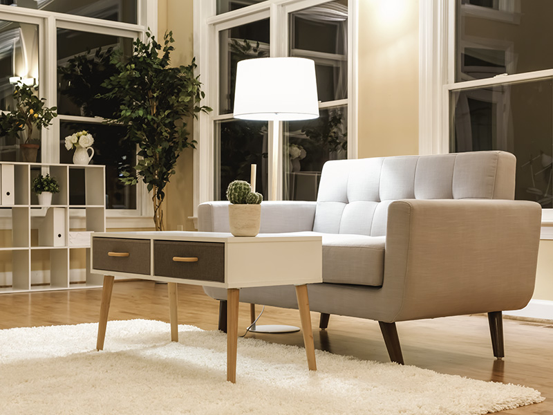 Large luxury interior home with gray midcentury loveseat and fluffy, cream coloured rug