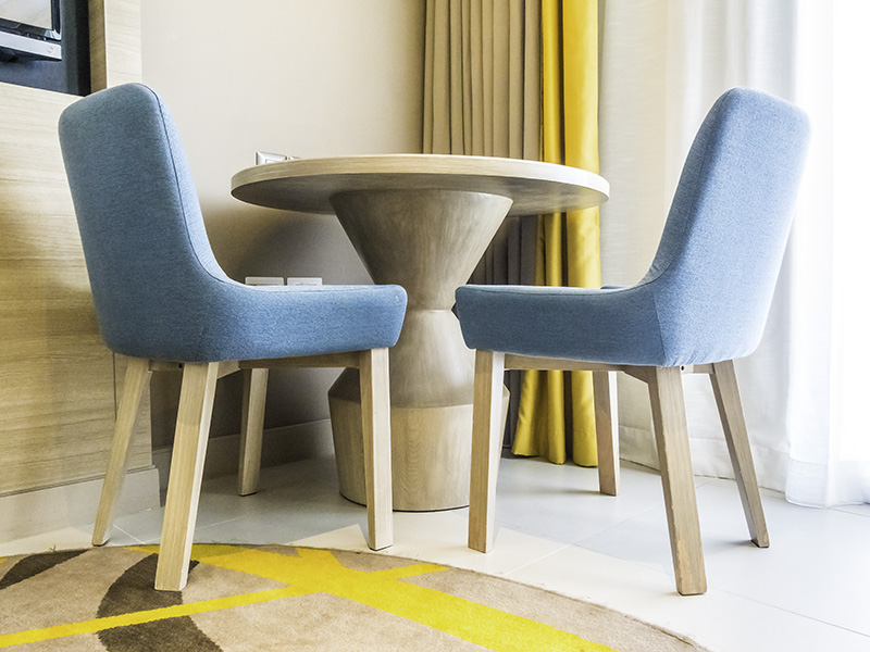 Mid-century modern table and teal coloured chairs with a bright geometric design rug