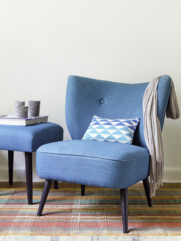 A teal mid-century design chair and side table against a neutral wall, with a brightly coloured rug underneath the chair